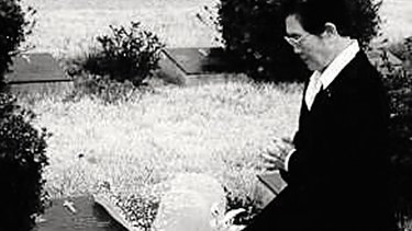 Korean War widow Kim Chung Kun lays flowers at Vincent Healy's grave several years after Mrs Healy's visit which inspired Mrs Kim's annual pilgrimage.