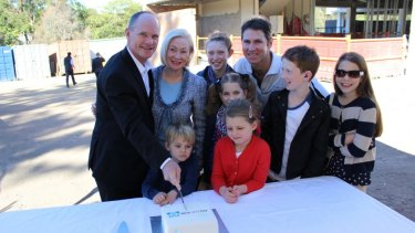 Premier Campbell Newman cuts cake with children and representatives of Hear and Say.