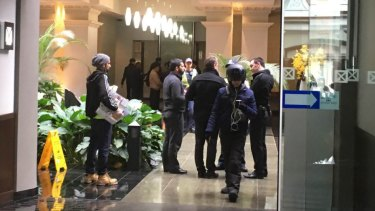 The family of the woman speak to police in the foyer of the building.