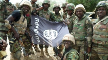 The Nigerian military pose with a flag of Boko Haram earlier this year.