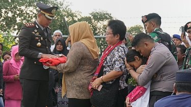 Brigadier Firman's widow receives the Indonesian flag from her husband's coffin as his younger brother Riswan, also an officer, consoles Firman's six-year-old daughter.