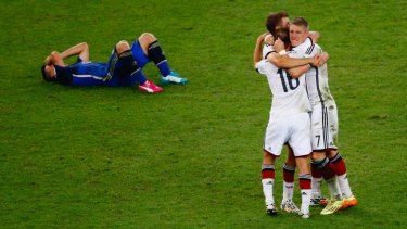 Germany celebrate as a a dejected Sergio Aguero of Argentina lies on the pitch.