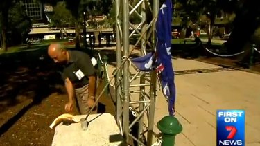 Peter Di Iorio sets fire to the Australian flag in Brisbane's Anzac Square just a day before Anzac Day.
