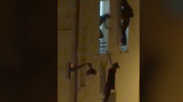 A woman dangles from the Bataclan window sill.
