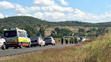 Emergency crews arrive at the scene where a light plane landed on the Capricorn Highway, about 25 kilometres south-west of Rockhampton.