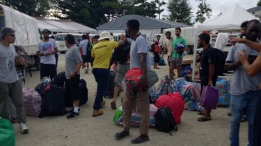 PNG immigration officers lead people out of the decommissioned detention centre on Friday.