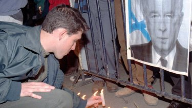 An Israeli places a candle in front of a portrait of Yitzhak Rabin outside his  Jerusalem residence on the morning after his assassination - Sunday, November 5, 1995.
