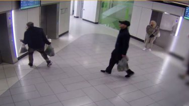 The man (centre) is seen waiting for a lift with two others, in CCTV footage.