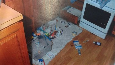Items strewn all over the kitchen floor, drawers open.