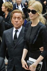 Italian designer Christian Valentino (L) and German model Claudia Schiffer attend the funeral service for late fashion designer Yves Saint Laurent in Paris June 5, 2008.