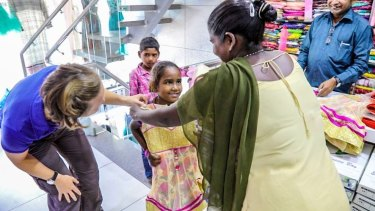 Krishna holds up a dress her to daughter Divya while shopping for supplies.