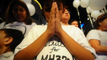 Hope: A young Malaysian boy prays at an event for the missing Malaysia Airlines plane in Kuala Lumpur in March 2014.