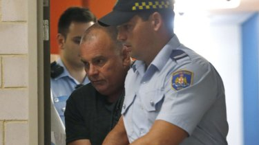 Glen McNamara is escorted from Kogarah local court after his arrest.