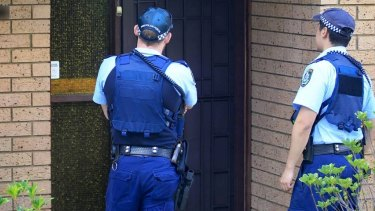Police officers at the home of the 16-year-old boy.