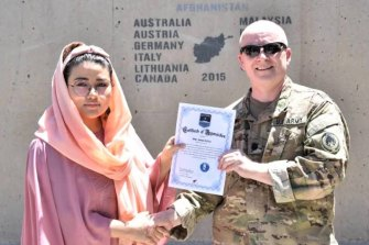 In this undated photo, Zainab Azizi receives a Certificate of Appreciation from a US Army member.