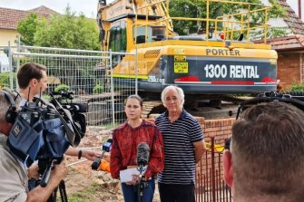 Toowong residents John Scott and Freya Robertson express their concerns as bulldozers remove Linden Lea at Toowong.