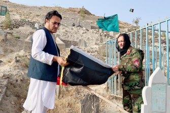 Zarifa Ghafari, right, at her father's grave last month.