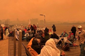 Locals and tourists on the Mallacoota wharf as bushfires surrounded the Victorian summer holiday spot on New Years Eve.
