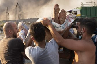 People evacuate wounded after the massive explosion in Beirut.