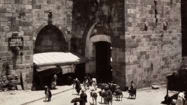 """An 1894 photograph from Maison Bonfils of Jerusalem's Jaffa Gate. A sign on the left directs visitors to """"Cook's Tourist Office"""". Thomas Cook began taking tourists to Palestine in 1869."""