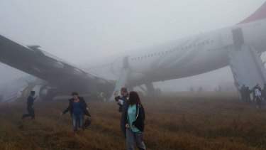 Passengers walk away from a Turkish Airlines plane after it skidded off the runway.