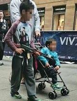 A boy walks through Martin Place with a toy AK-47.