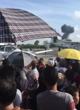 The crowd watches as smoke rises from the crash of a Gripen jet at Hat Yai Airport.