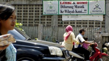 People negotiate the traffic past a banner put up by the hardline Islamic Defenders Front calling for gay people to leave the Cigondewah Kaler area in Bandung, West Java, Indonesia.