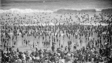 Crowds sunbathing and swimming at Bondi Beach, Sydney, ca. 1930's.