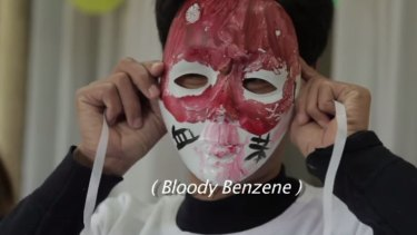 In the film, 'Who pays the price?' a protester objects to the use of benzene in smartphone production.
