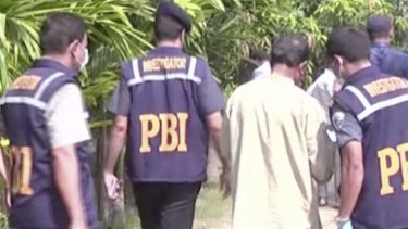 Investigators work at the site in northern Bangladesh where Kunio Hoshi, 50, was killed by two masked men.