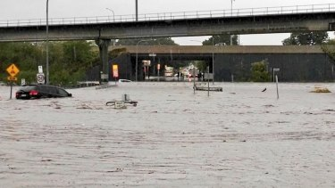 Queensland weather. A car floats away on what was previously roadway near Toombul Shopping Centre.