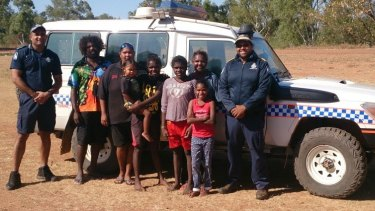 The heroic police officers pose with the group they saved in far north Queensland.
