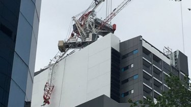 Workers dangle from a collapsed crane at a North Sydney building site.