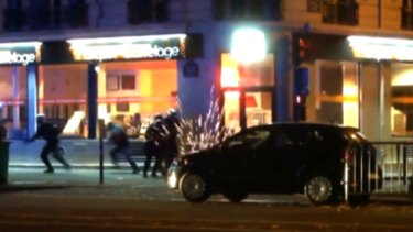 Sparks can be seen as bullets ricochet by a car near the Bataclan theatre.