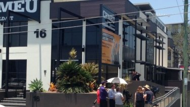 Staff and media gather as the Brisbane office of the CFMEU is raided by federal police.