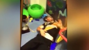 An Albury Tigers player on the floor of a children's play area in the hospital.