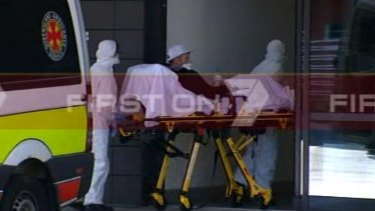 A man suspected of suffering from Ebola is wheeled into the Gold Coast University Hospital.