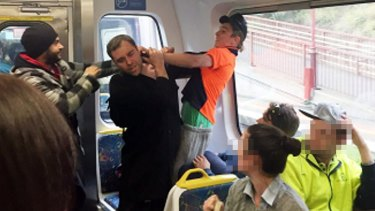 Jason Cias (centre) is assaulted by the man wearing orange after defending three women from abuse on a Craigieburn train.