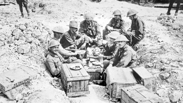 Soldiers having breakfast in a shell hole.
