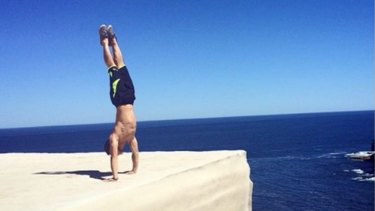 A man performs a handstand near the edge of Wedding Cake Rock.