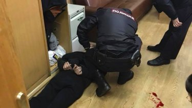 Police officers detain the unidentified man in the offices of the Echo of Moscow radio station.