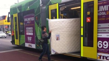 A new mattress heads to its new home via public transport in Melbourne.