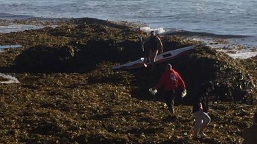 Surfers cross over the piles of seaweed dumped at Burleigh.