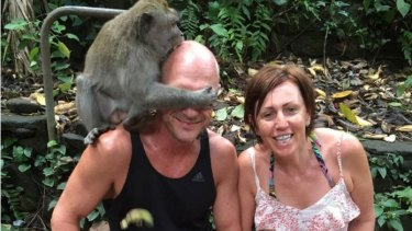 A monkey bites Anthony Wallace on the head as he sits next to girlfriend Libby McManus at Ubud Monkey Forest in Bali.