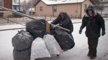 A pair of scrappers fight blizzard conditions to deliver their haul of aluminium cans to the scrapyard. They may earn $30 to $50 for the lot.