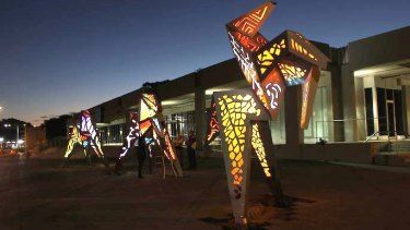 The Origami Horses  lit up at night in West Ryde plaza.