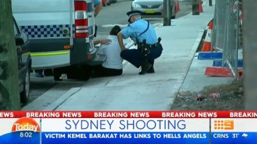 A distressed man at the scene of Kemel Barakat's shooting is treated by paramedics.