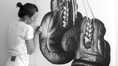 CJ Hendry puts the finishes touches to a pair of boxing gloves that attracted the attention of world champion pugilist Floyd Mayweather.
