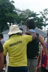 A photo tweeted by a refugee on Friday morning showing a man being led away by immigration authorities.